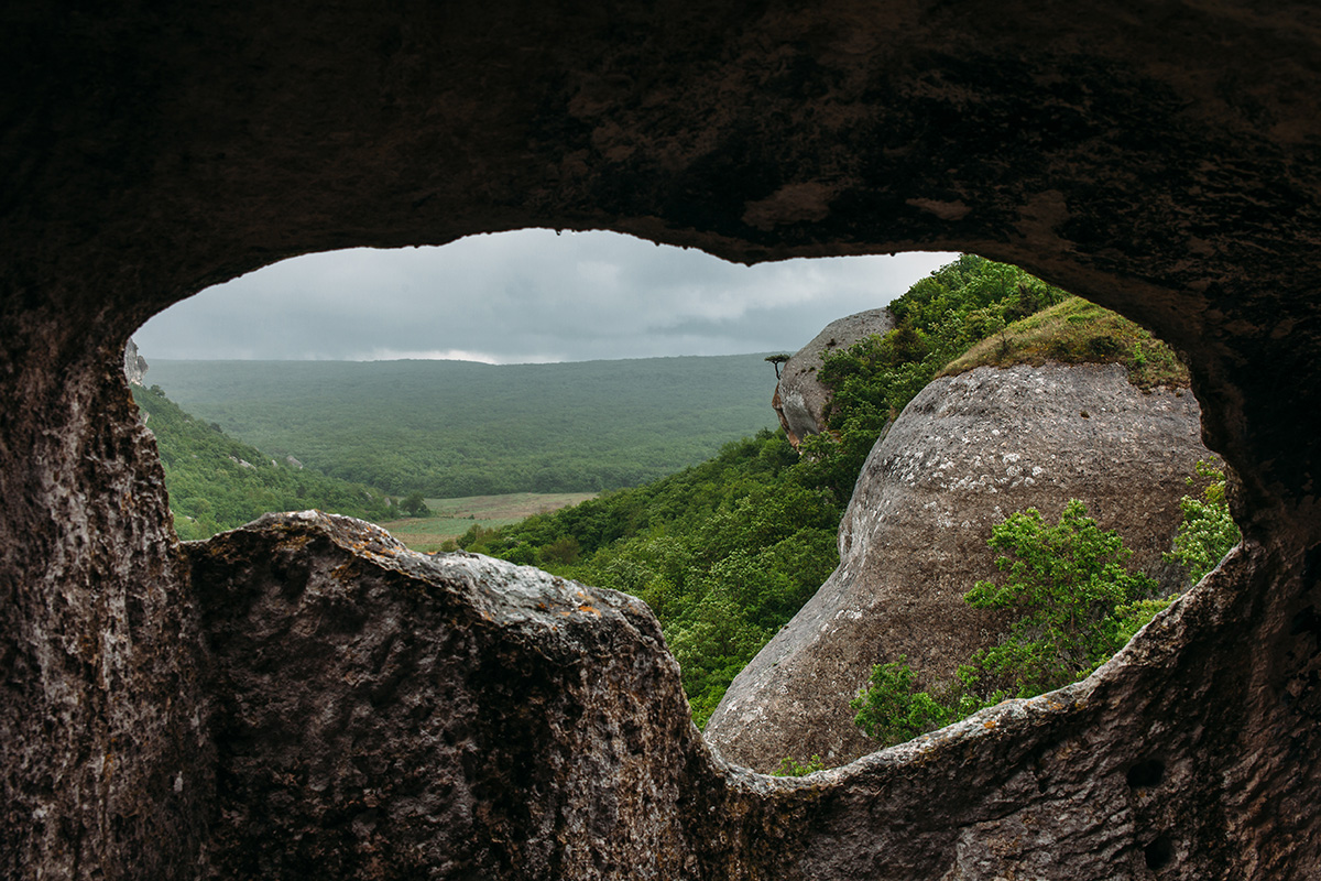 View from the ancient cave to the green mountain forest valley. Landscape in the Crimean mountains